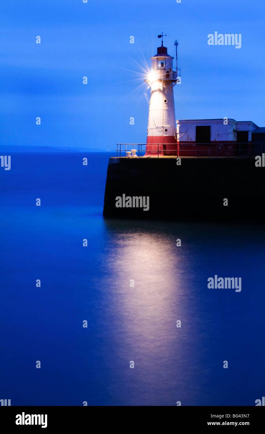 Der Leuchtturm am Ende der Newlyn Pier in der Morgendämmerung, lange Belichtung, Newlyn, Cornwall, UK Stockbild