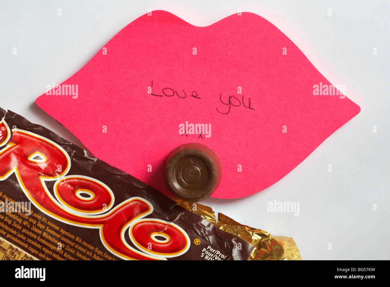 Liebe Dich - Die letzte Rolo - Liebe Sie xx auf rosa Lippen geschrieben Post it Note mit der letzten Rolo des Pakets Stockfoto