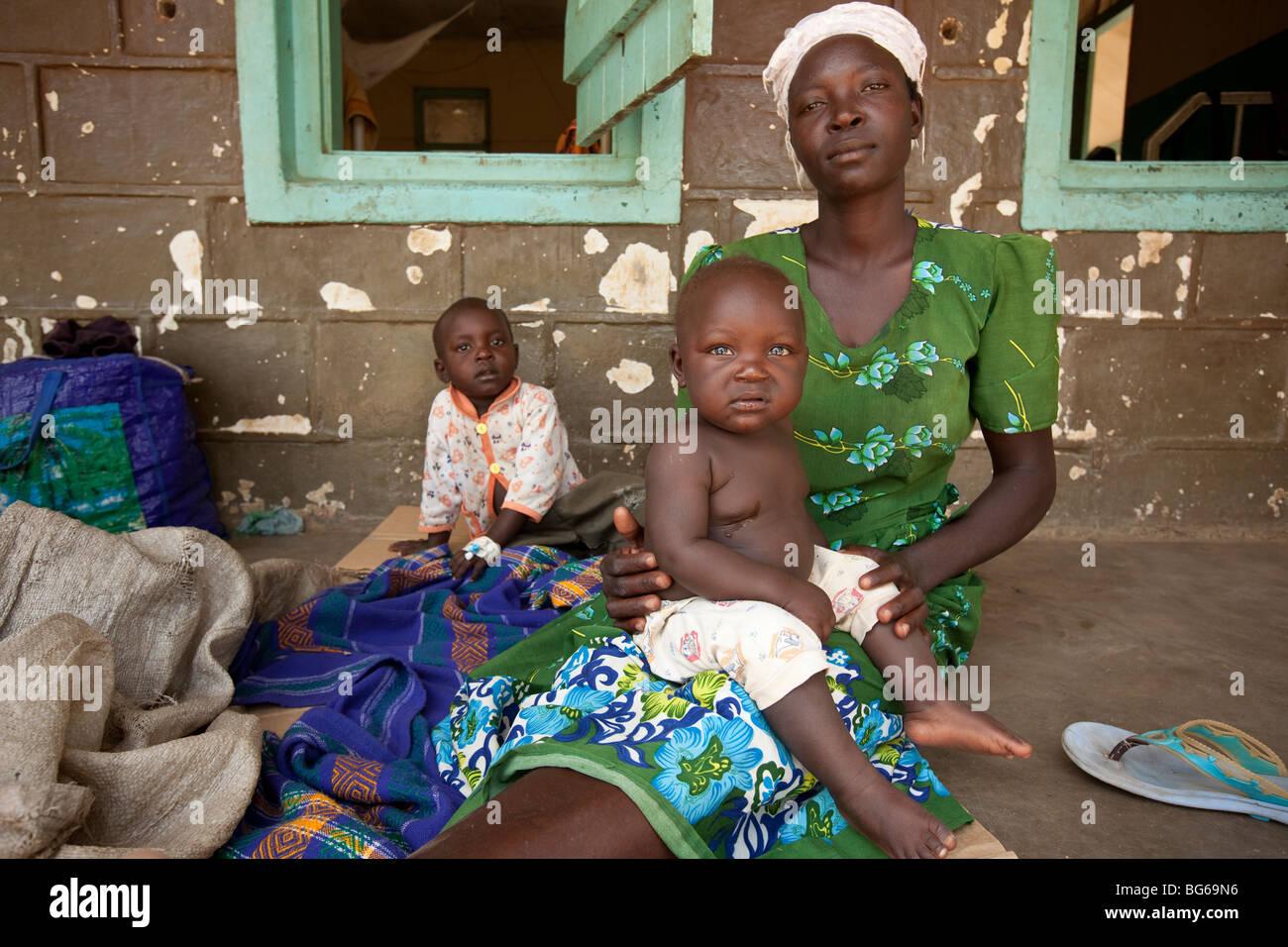 Eine Mutter bringt ihre kleinen Kinder in ein Krankenhaus für Malaria Behandlung, Amuria, Uganda, Ostafrika. Stockbild