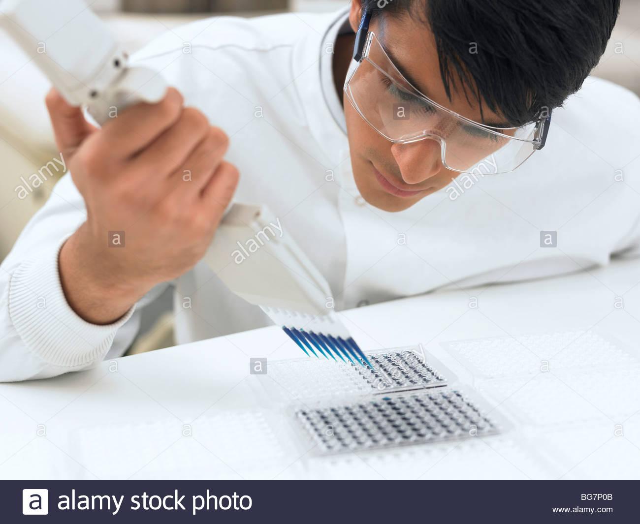 Wissenschaftler fallen Flüssigkeit im Behälter Stockbild