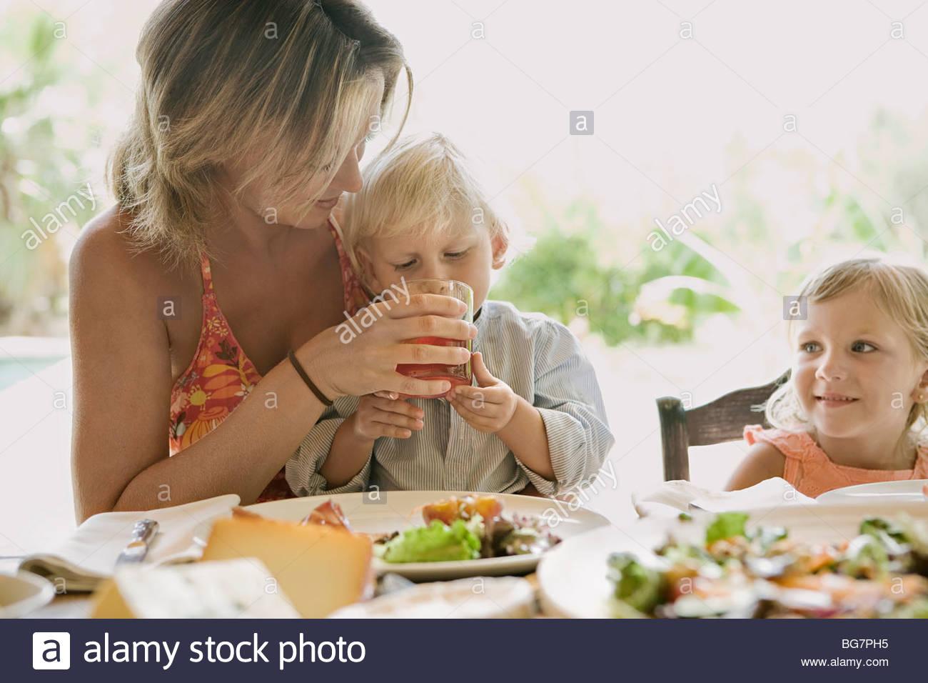 Mutter hilft Sohn am Tisch trinken Stockbild
