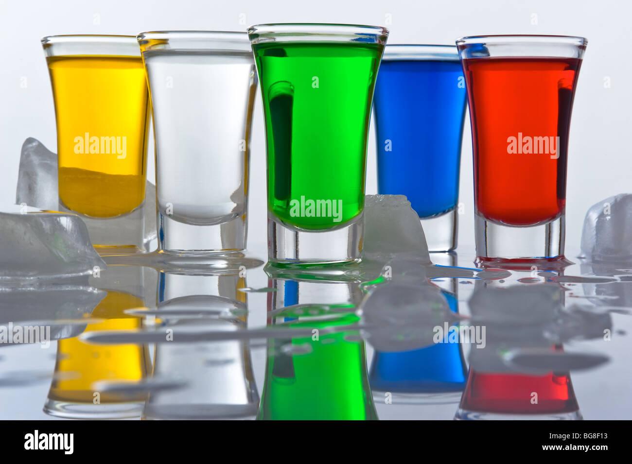 Stillleben aus fünf kleinen Haufen aus dem Glas gefüllt Farbe Cocktails mit Überlegung und Eis Stockfoto