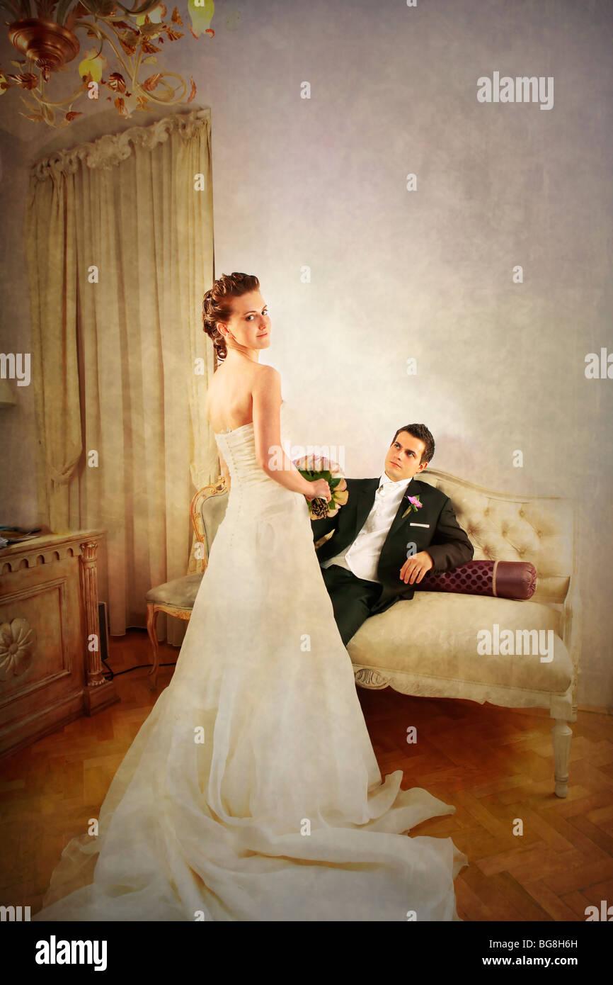 Voller Länge von Braut und Bräutigam in luxuriös und mit einem Vintage look innen mit Kleid von hinten Stockbild