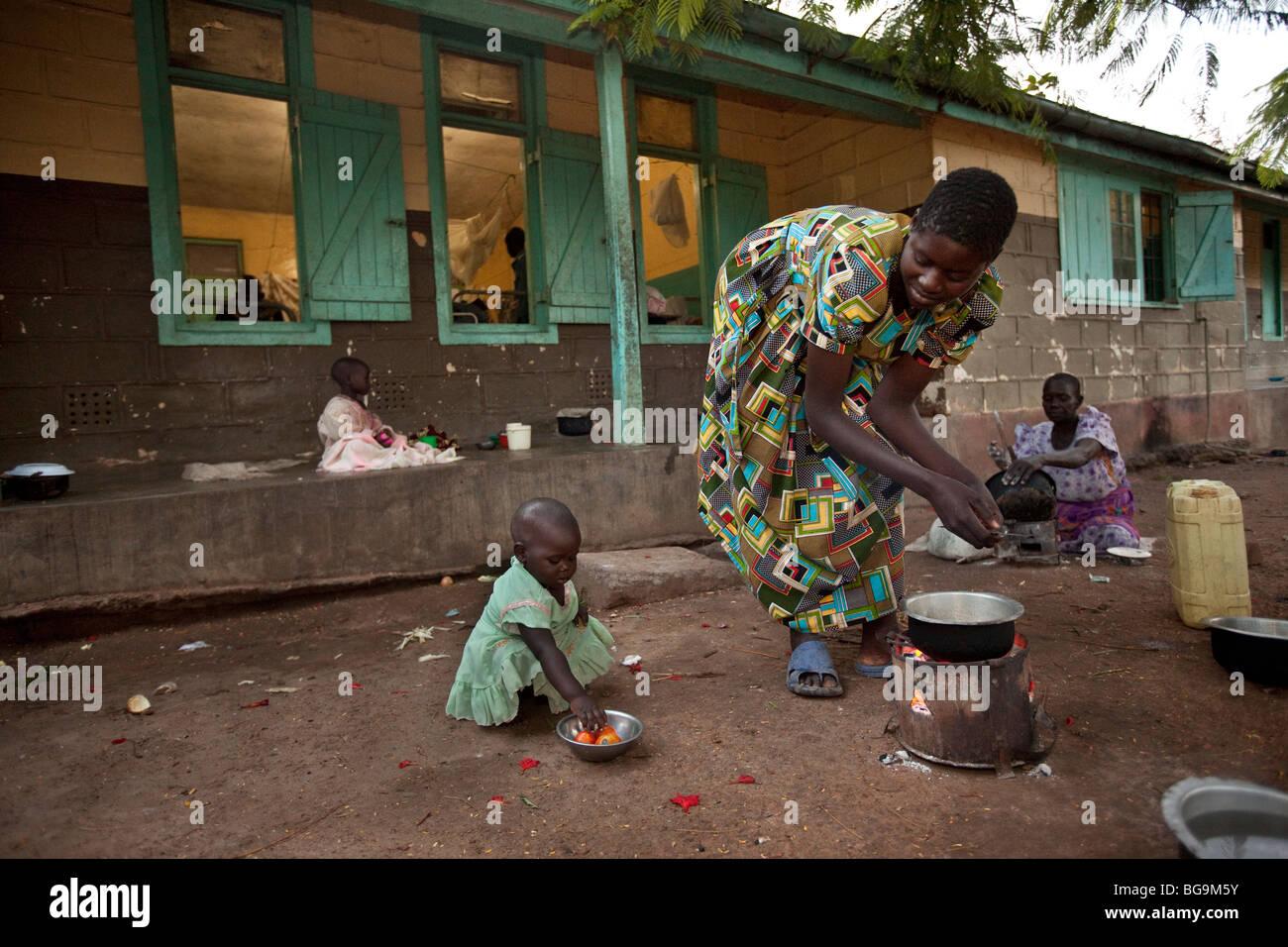 Eine Frau kocht für ihre Familie draussen das Krankenhaus in Amuria, Uganda, Ostafrika. Stockbild