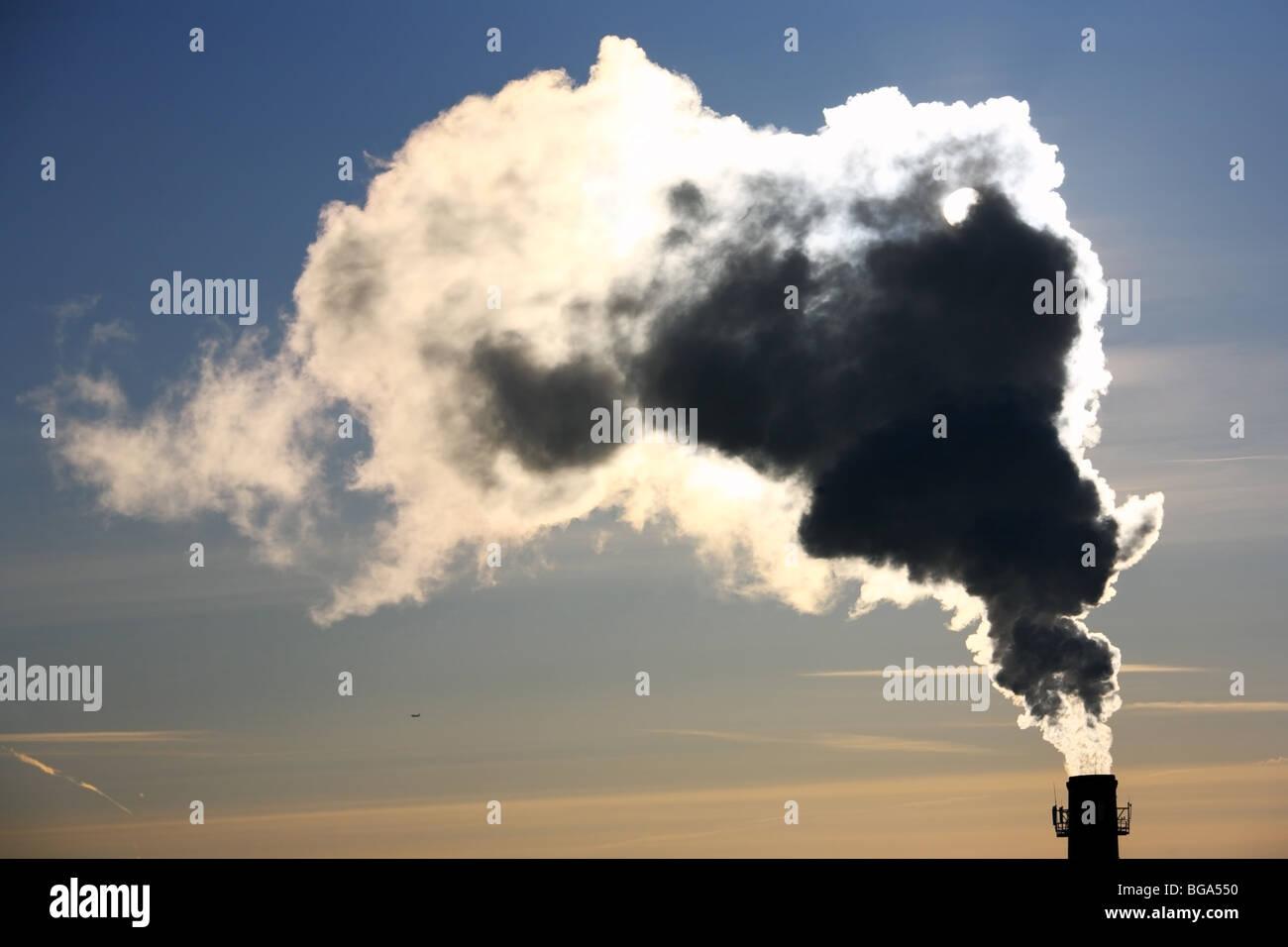 Verschmutzung. Dicker Rauch aus dem Schornstein in Wintermorgen. Stockbild