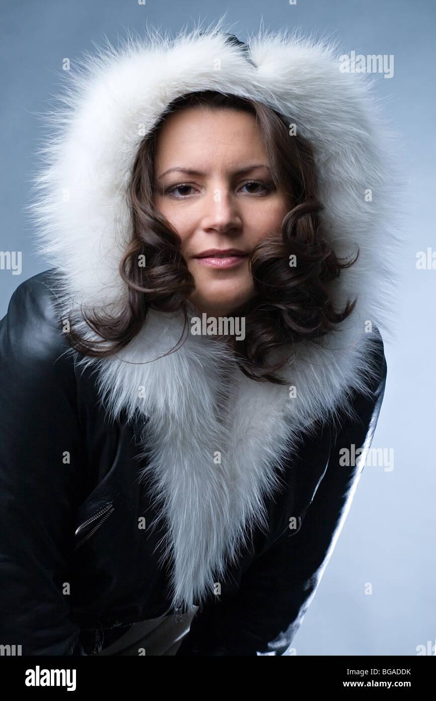 b395360bb9c3 schöne Frau im schwarzen Parka mit weißem Fell auf blauem Hintergrund  Stockbild