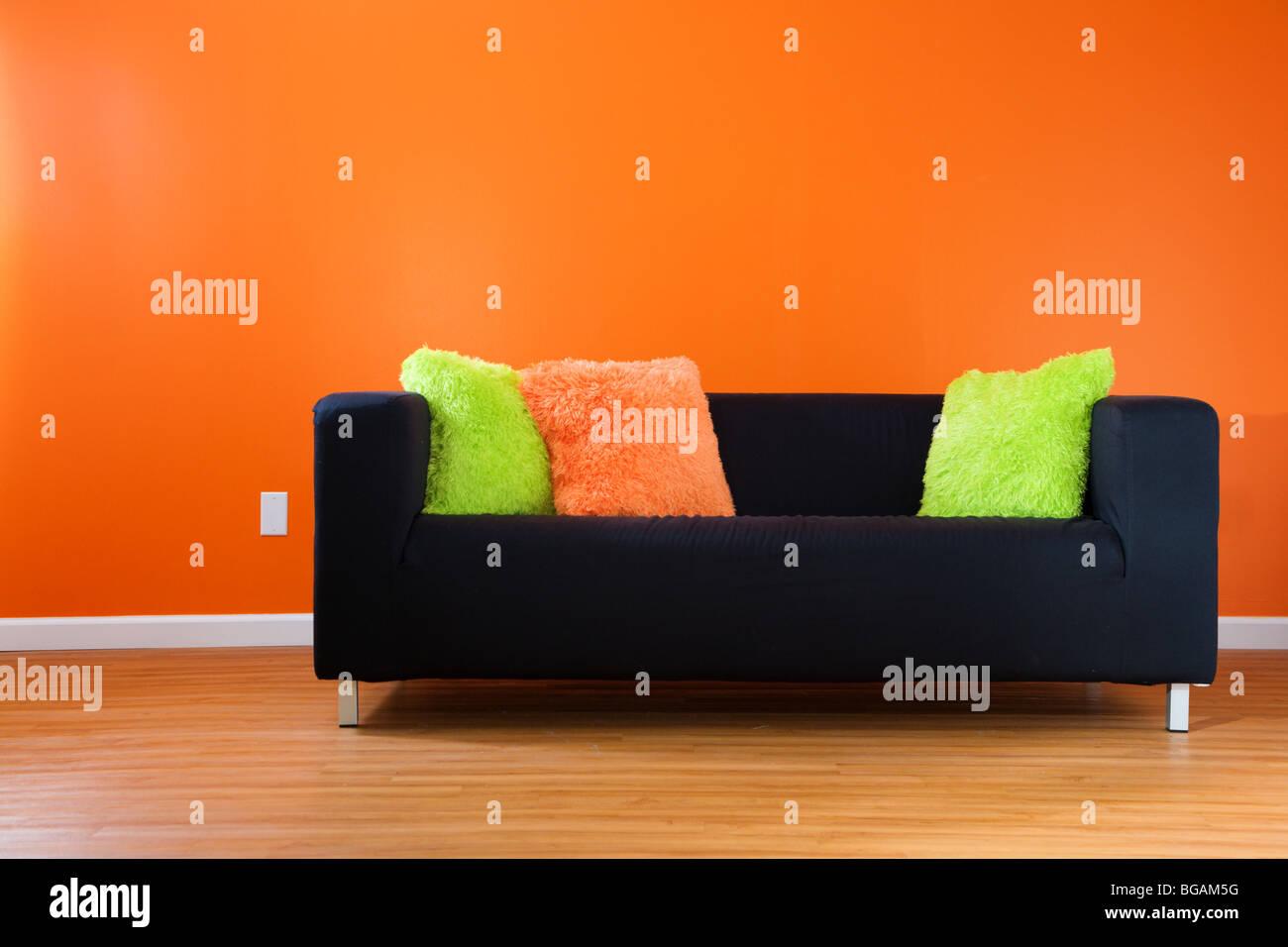 Zeitgenössische schwarze Couch gegen helle orange Wand in einem modernen Wohnzimmer Stockbild