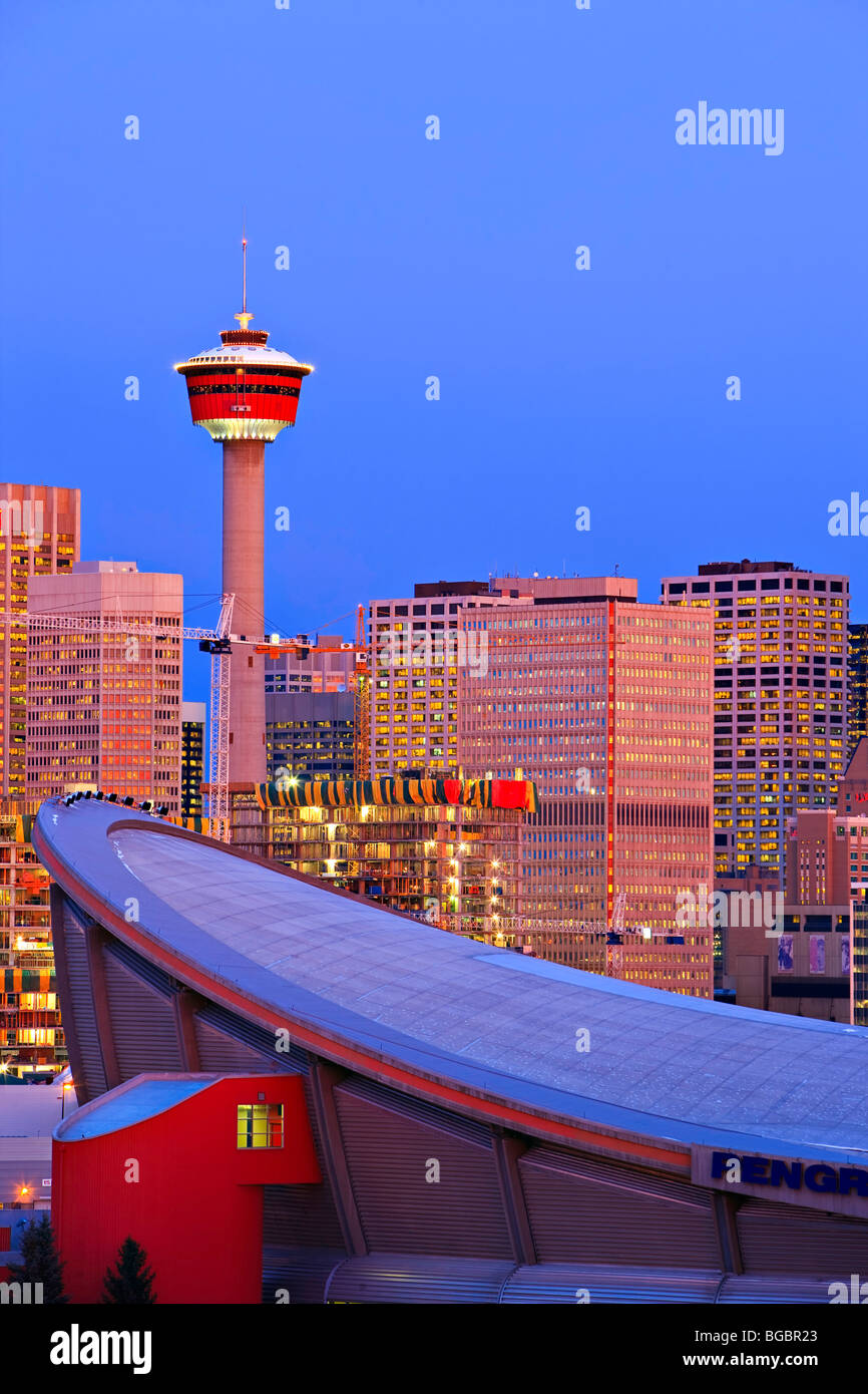 Der Saddledome mit Hochhäusern und dem Calgary Tower im Hintergrund bei Sonnenaufgang, Stadt von Calgary, Alberta, Stockbild