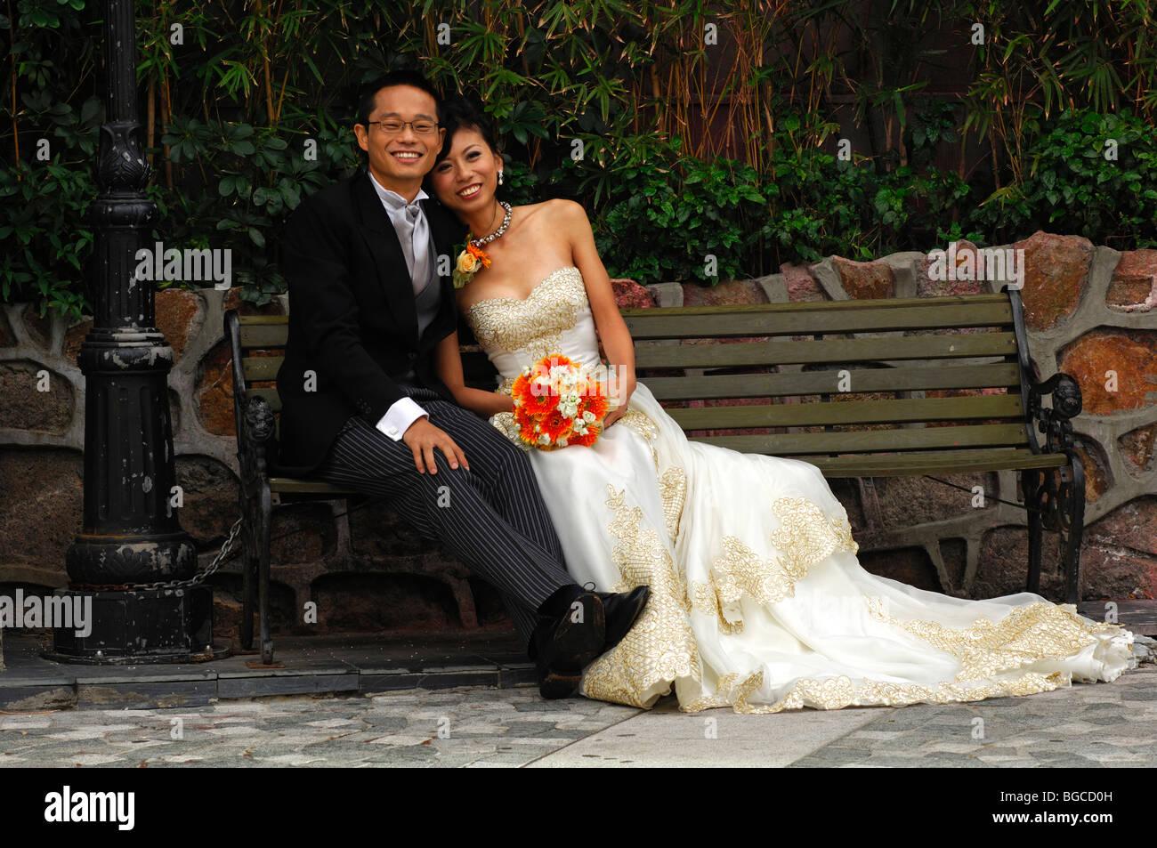 Chinesische Braut und Bräutigam in langen Brautkleid und dunklen ...