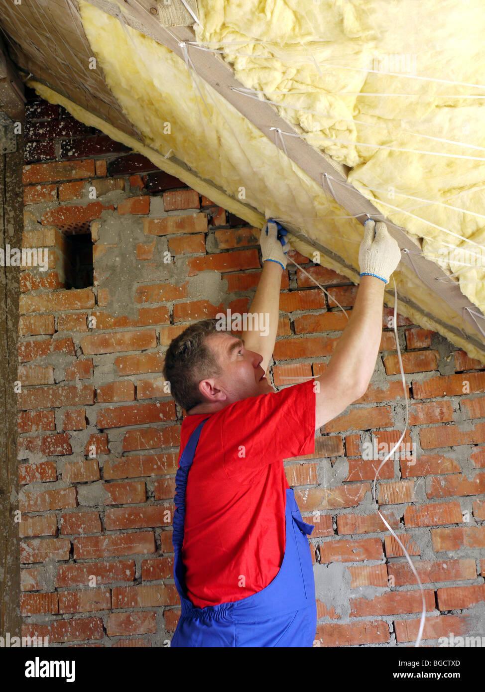 Bauarbeiter, die thermisch isolierende Haus Dachboden mit Mineralwolle Stockbild