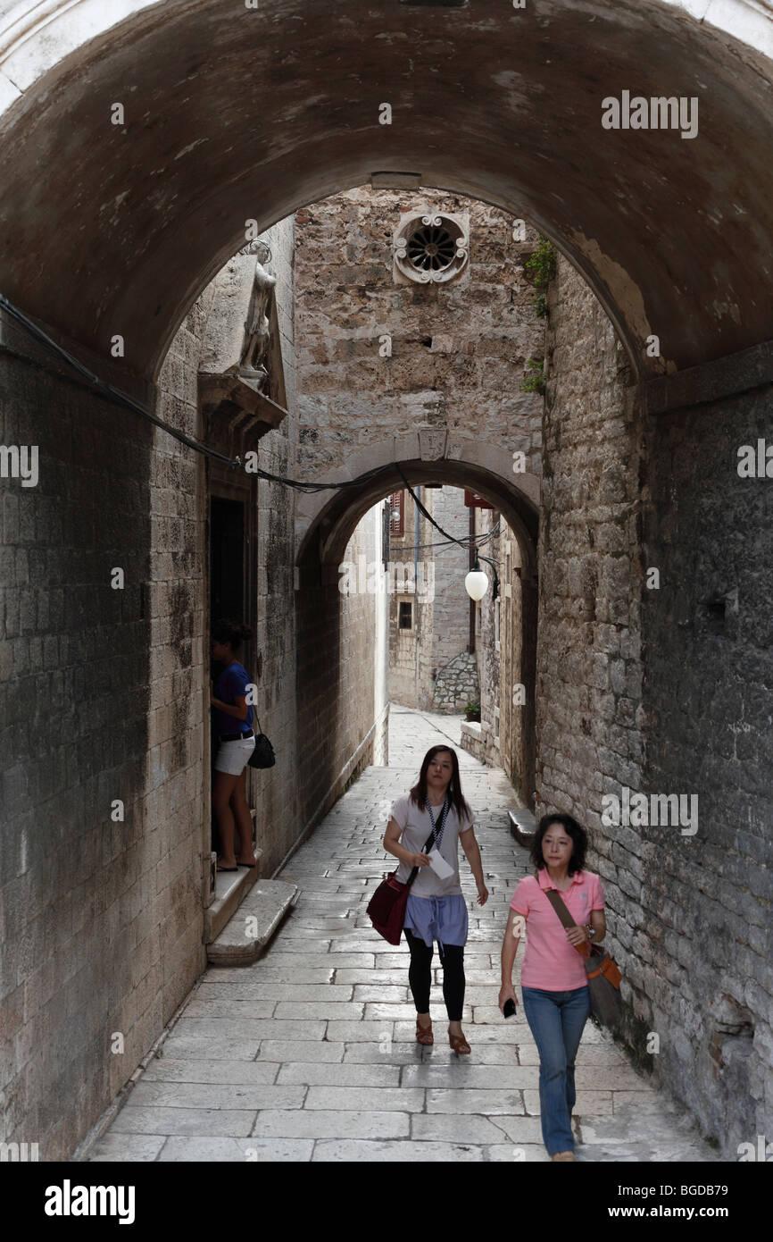 Asiatische Touristen in einer alten Stadt Lane, Sibenik, Dalmatien, Adria, Kroatien, Europa Stockbild