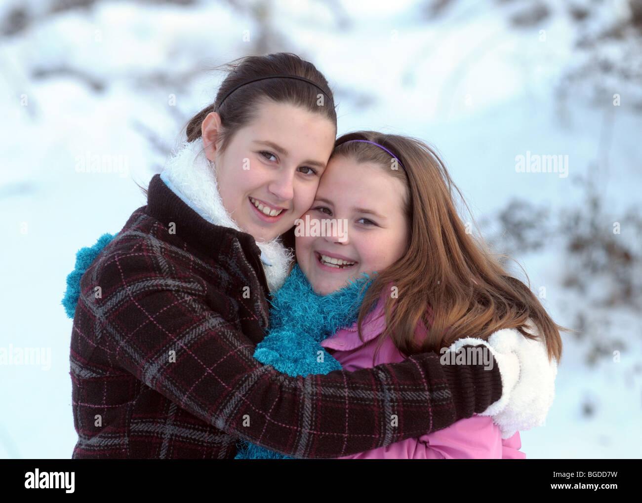 Schwestern glücklich umarmen sich bei kaltem Wetter Stockbild