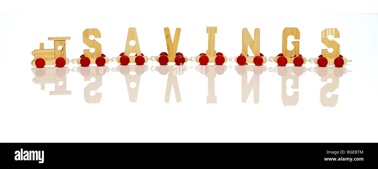 """Eine Spielzeugeisenbahn mit Buchstaben bilden das Wort """"Einsparungen"""" Stockbild"""
