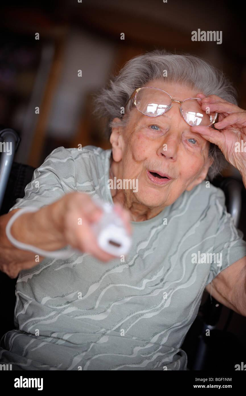 Ein Rentner hebt ihre sectacles während der Wiedergabe die Nintendo Wii. Stockbild