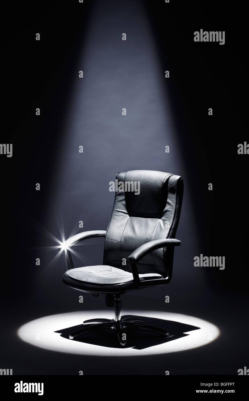 Leere schwarze Ledersessel unter Spotlight-Mastermind Stockbild