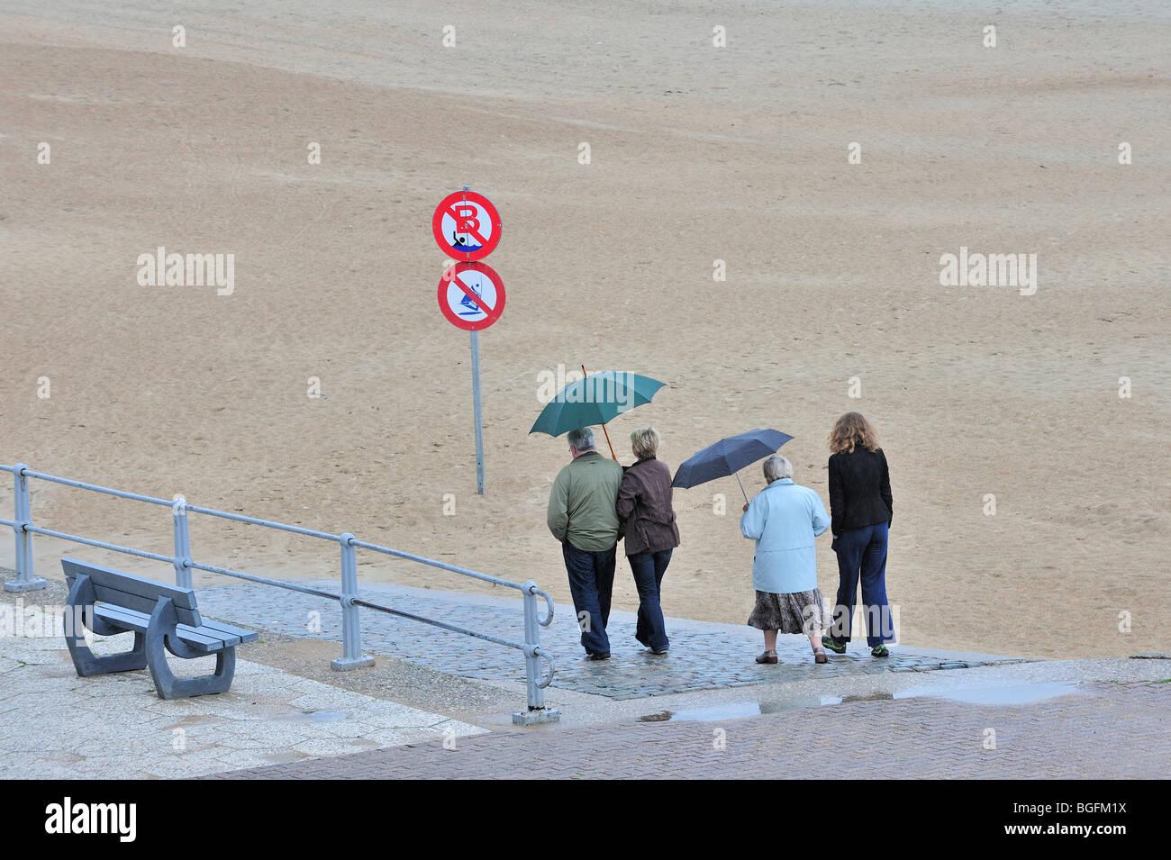 Touristen mit Sonnenschirmen zu Fuß über den Deich entlang Strand an einem regnerischen Tag in den Sommerferien Stockbild