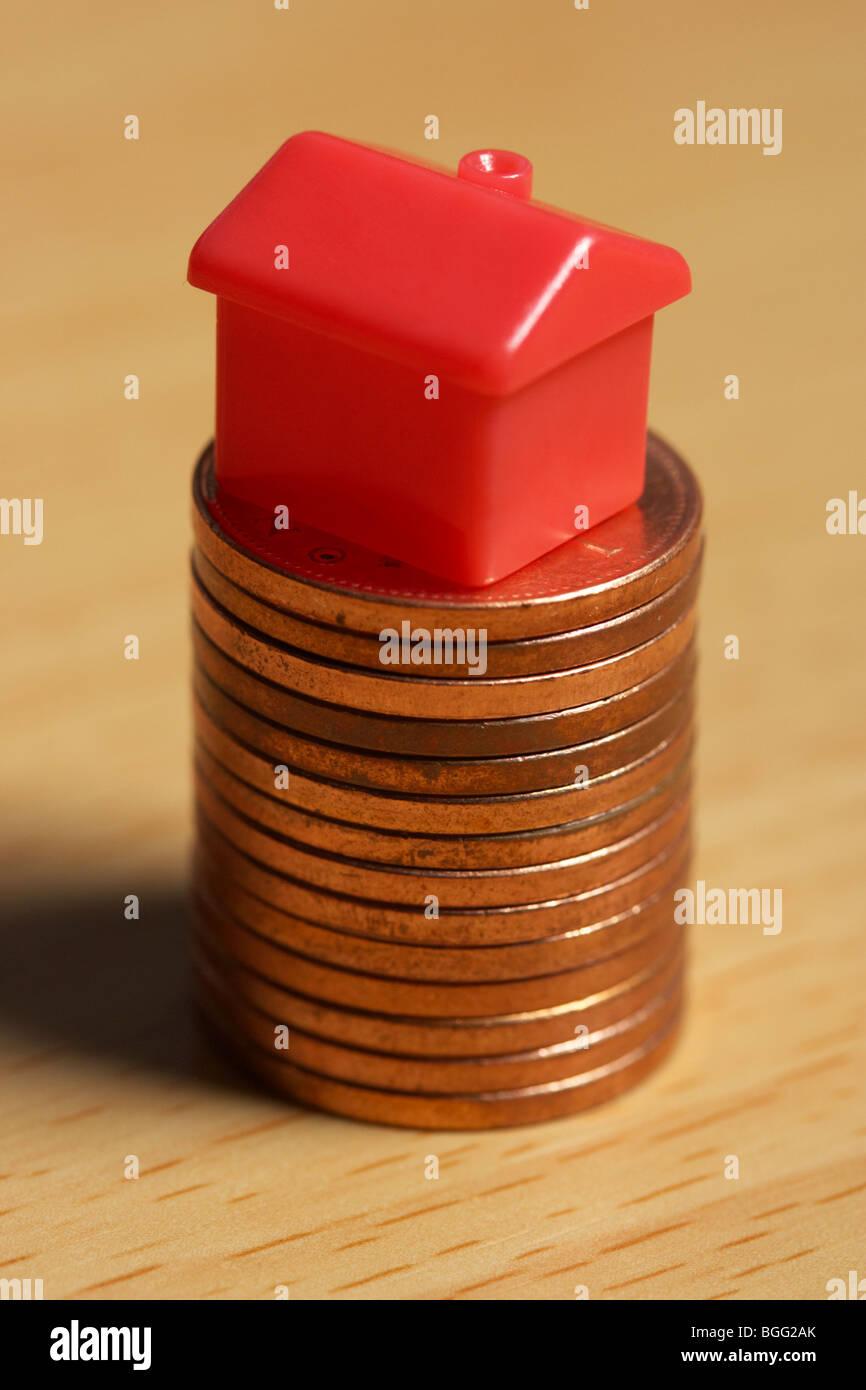 kleines Modell Spielzeug Haus auf einen Stapel von Penny-Münzen Stockbild