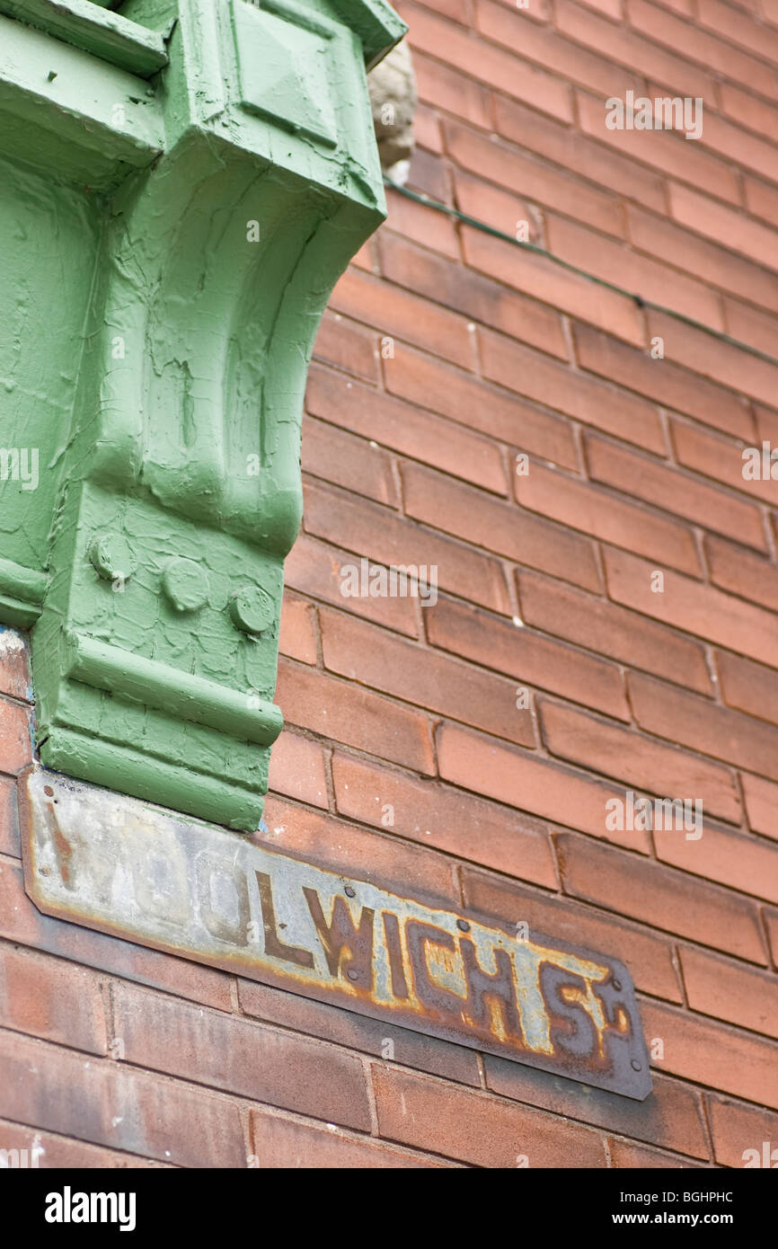 Eine alte rostige Straßenschild auf einer roten Backsteinmauer, an der Ecke ein grünes Fenster-Gehäuse, Stockbild