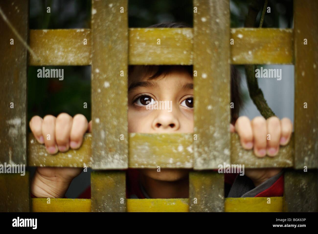 Jungen im Alter von sieben Jahren versteckt sich hinter Gitter Stockbild