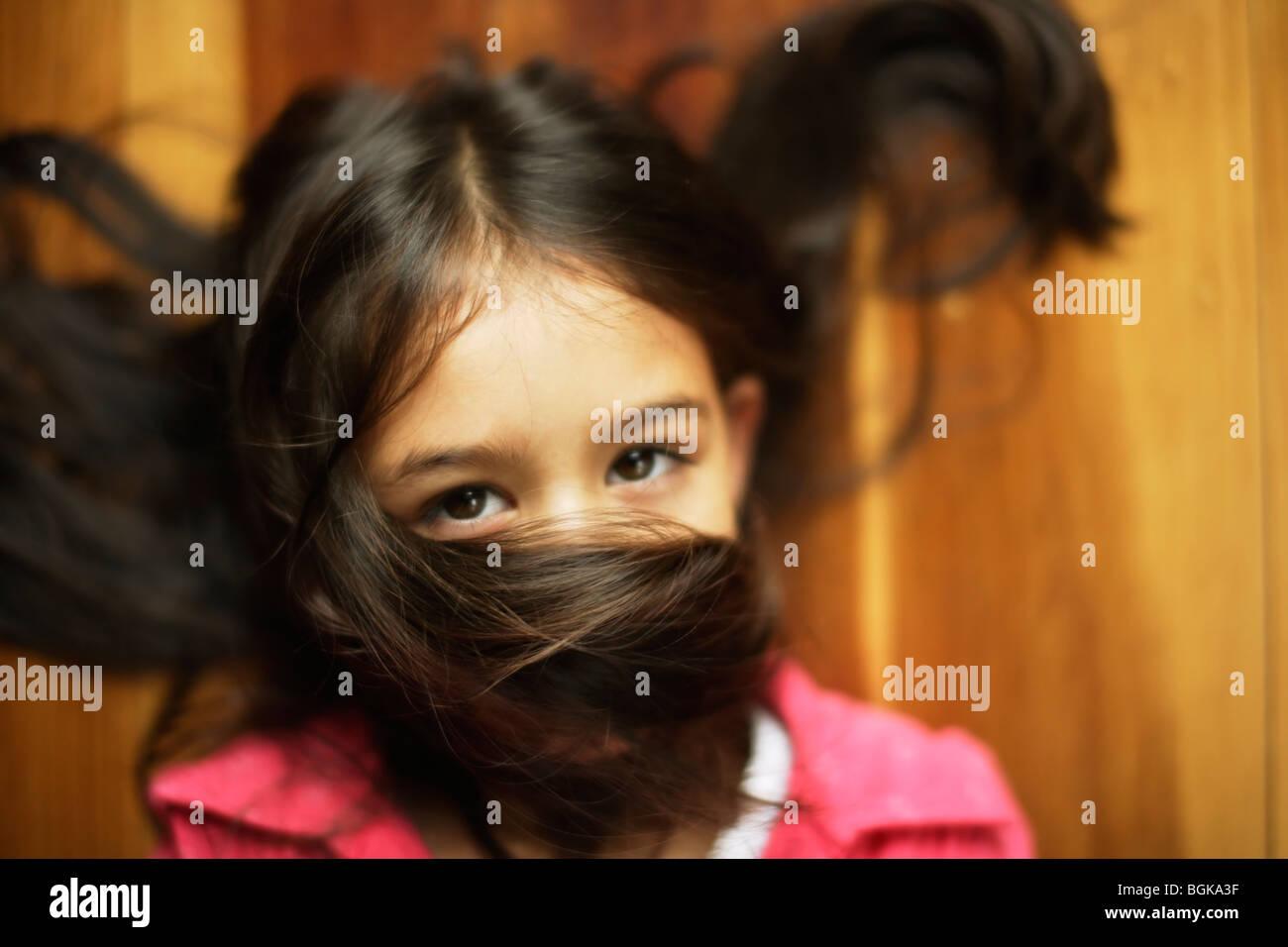 Mädchen von sechs Jahren mit Haaren über Gesicht Stockbild