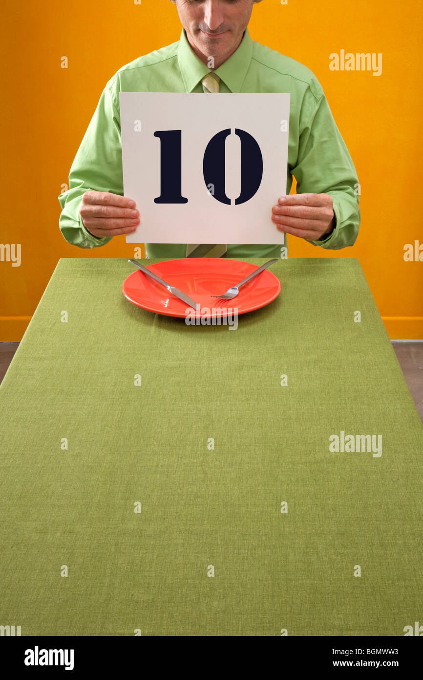 Mann am Tisch Essen hält 10 Zeichen zum Preis Essen Stockbild