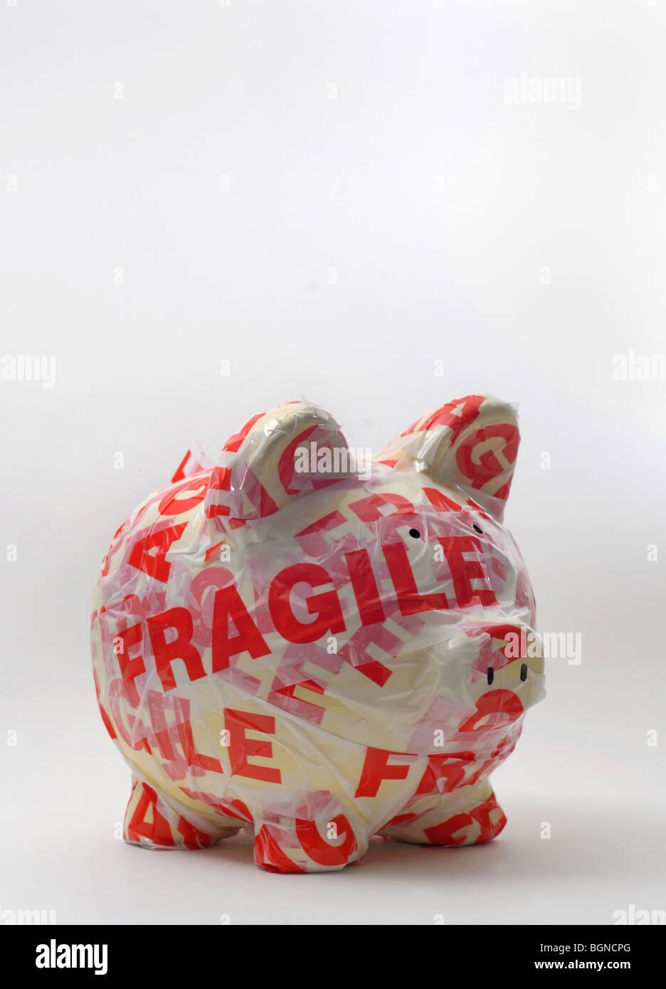 PIGGY BANK IN FRAGILEN WARNUNG GEWICKELT BAND RE/INVESTITIONEN/GELD/WIRTSCHAFT/SPARKASSEN DER WIRTSCHAFT GELD UK Stockbild