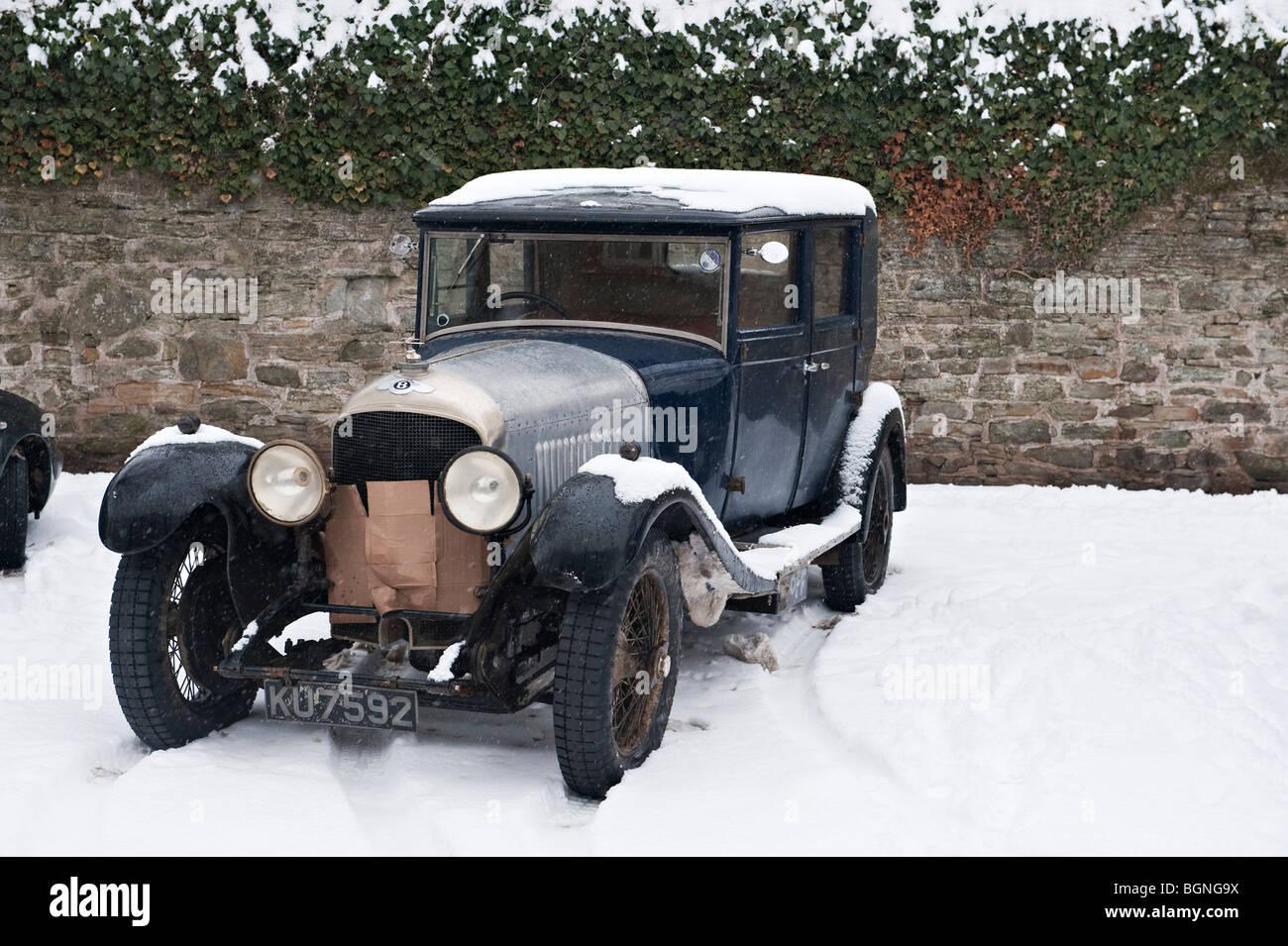 Ein Jahrgang Bentley in den Schnee, den Kühler vor der Kälte geschützt geparkt Stockbild