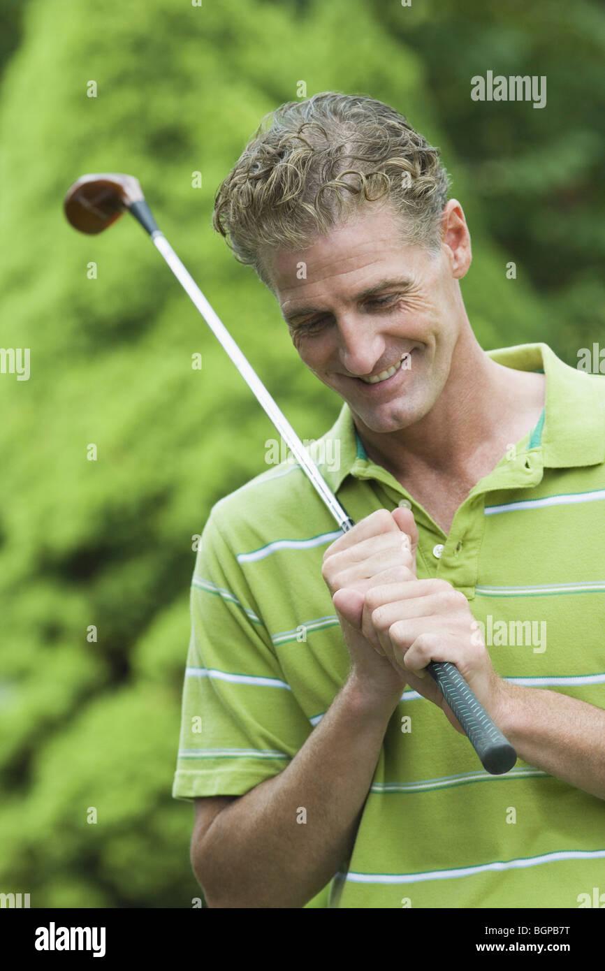 Nahaufnahme von einem reifen Mann hält einen Golfschläger und lächelnd Stockbild
