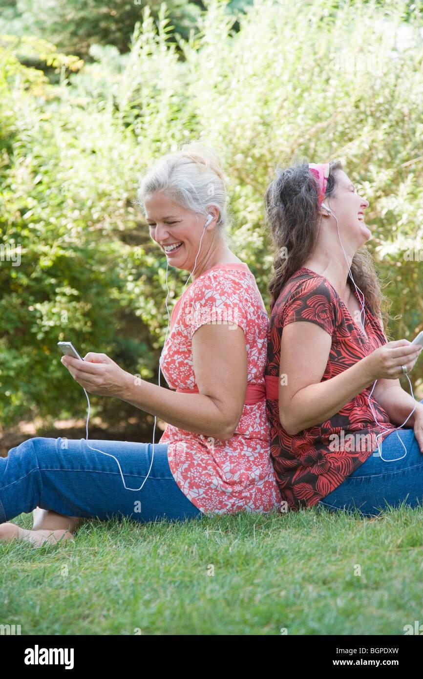 Seitenansicht der zwei Reife Frauen sitzen Rücken an Rücken in einem Park und anhören von MP3-Playern Stockbild