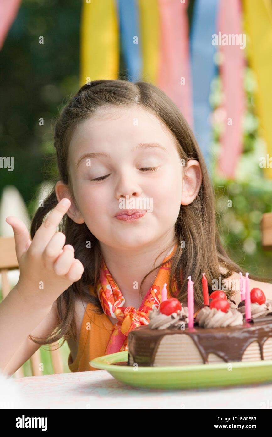 Mädchen Verkostung einen Geburtstagskuchen Stockbild