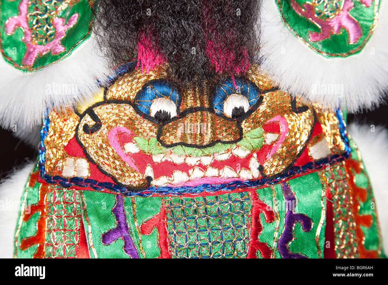 Nahaufnahme einer handgefertigten chinesische ornamentalen Robe sportliche das Gesicht eines Löwen Stockbild