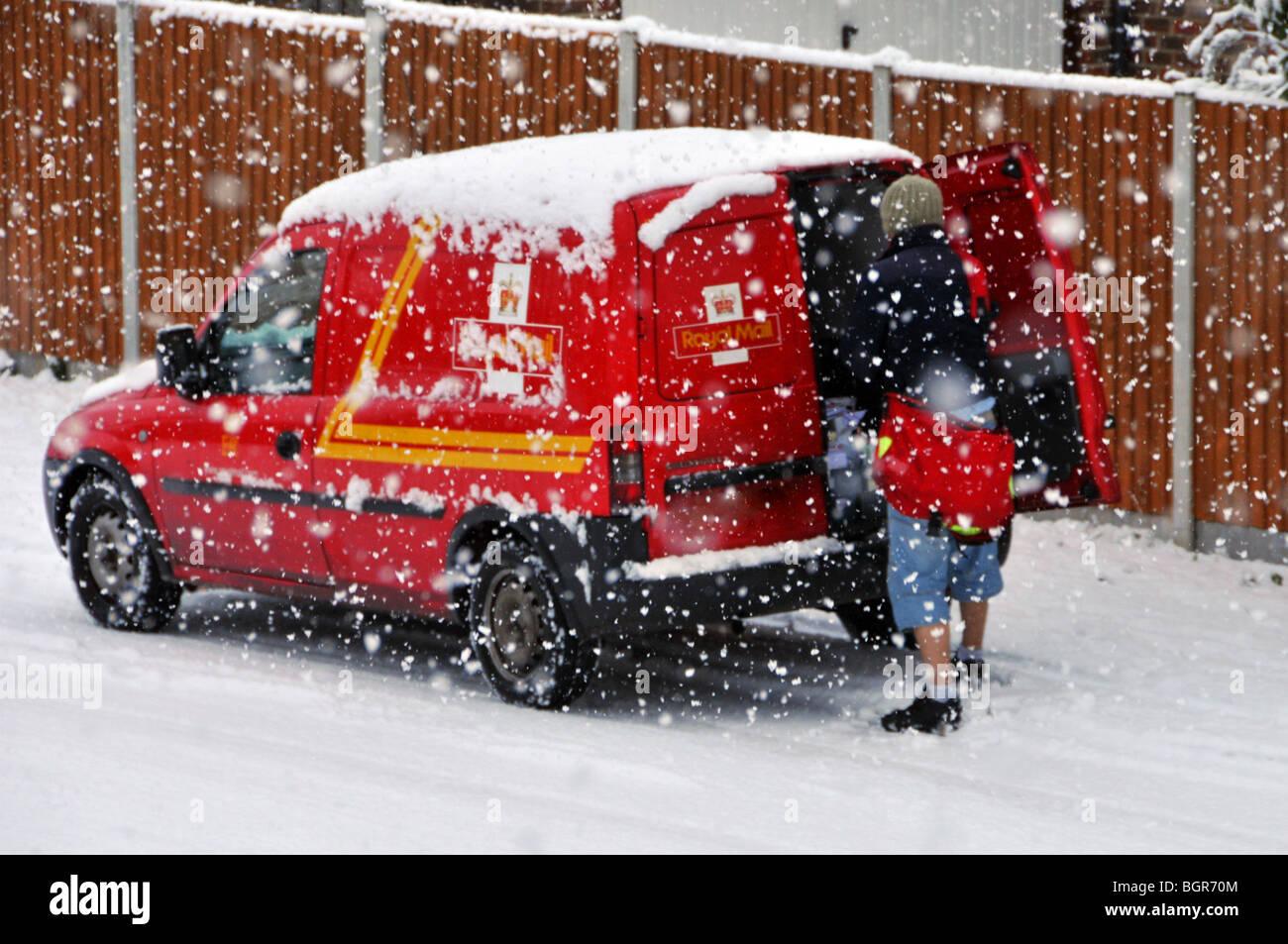 Royal Mail Lieferwagen und Postman in Wohnstraße in Schnee Sturm Nummernschild verdeckt Stockbild
