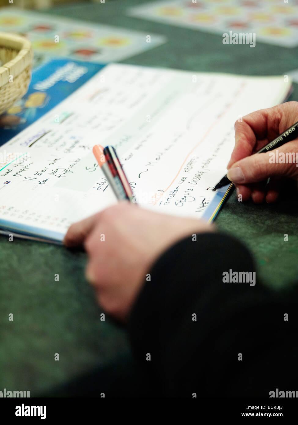 Die Hände einer Person in einem Kalender zu schreiben. Stockfoto
