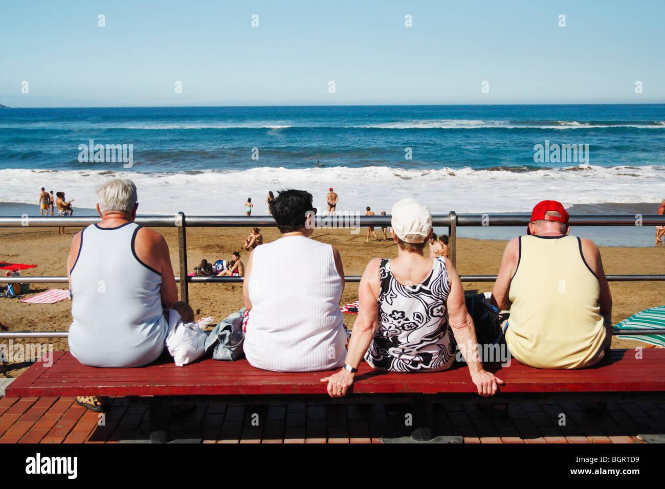 Zwei ältere Ehepaare, die Surfer am Strand in Spanien zu beobachten Stockfoto