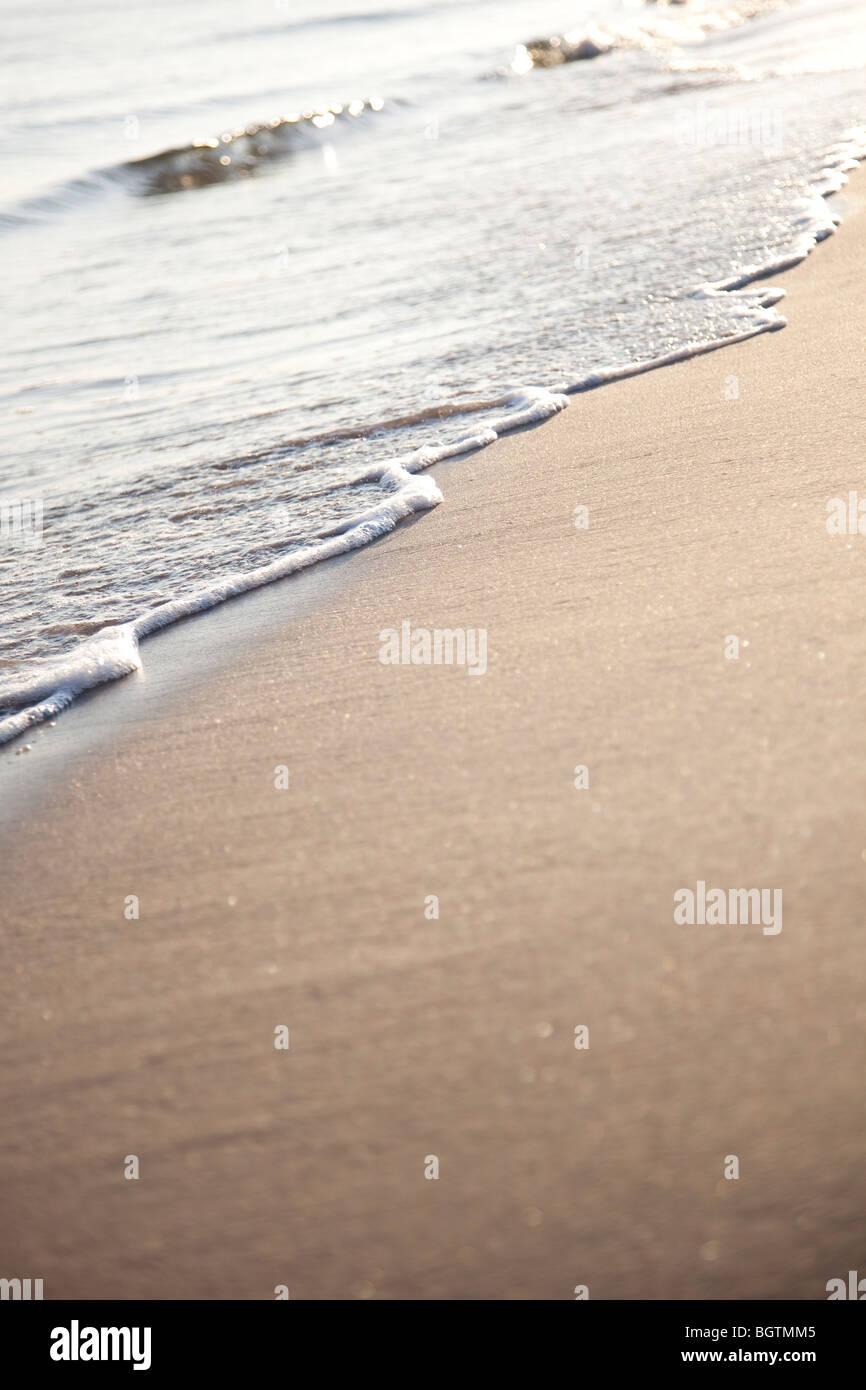 Sanfte Brandung gegen einen goldenen Ufer plätschern Stockbild