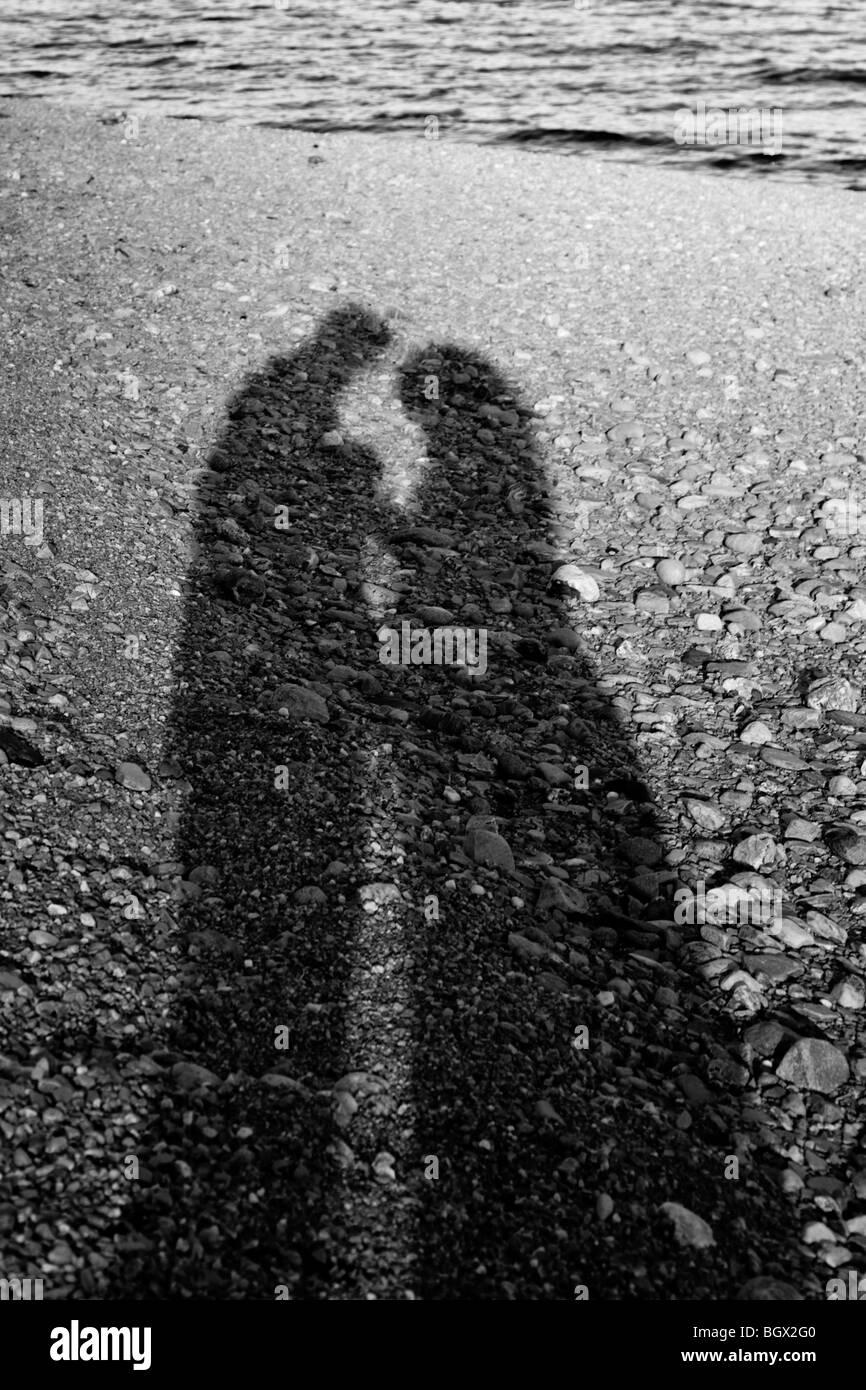 Schatten eines Paares an einem steinigen Strand Stockfoto