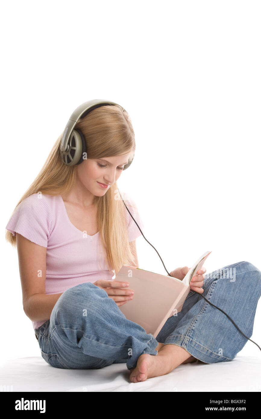 Teenager-Mädchen sitzen mit gekreuzten Beinen, Musikhören und Buch Stockfoto