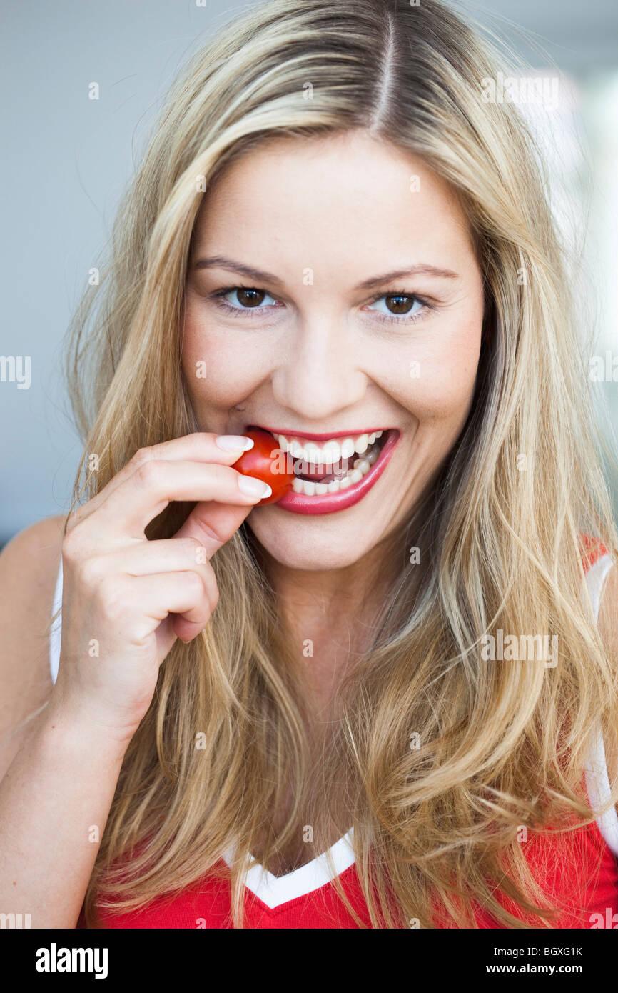 Junge Frau knabbert an Tomaten Stockbild