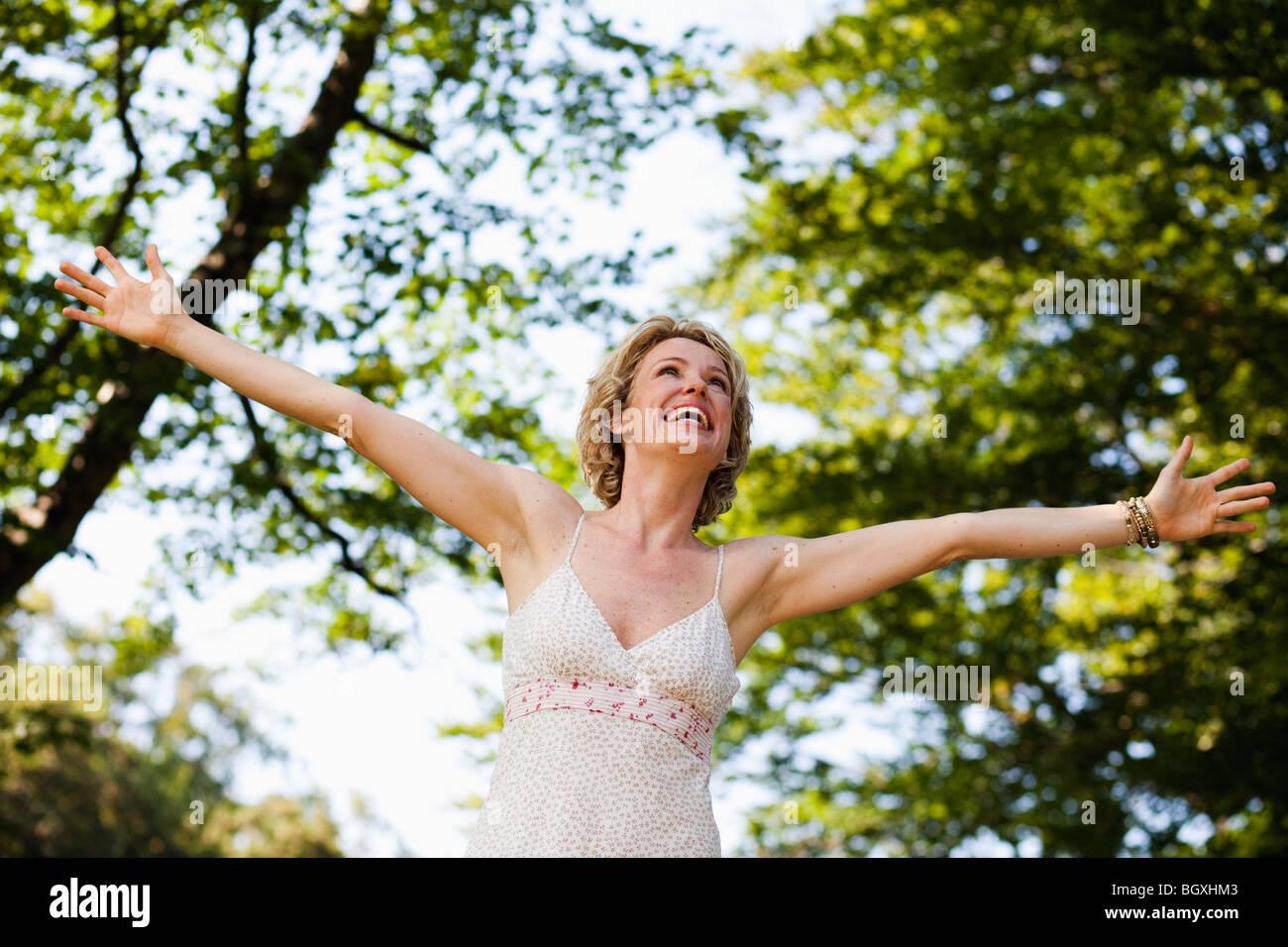 Frau mit weit offenen Armen Stockbild