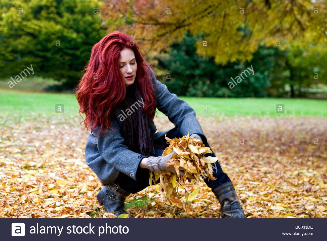 Eine junge Frau, die Blätter im Herbst sammeln Stockbild