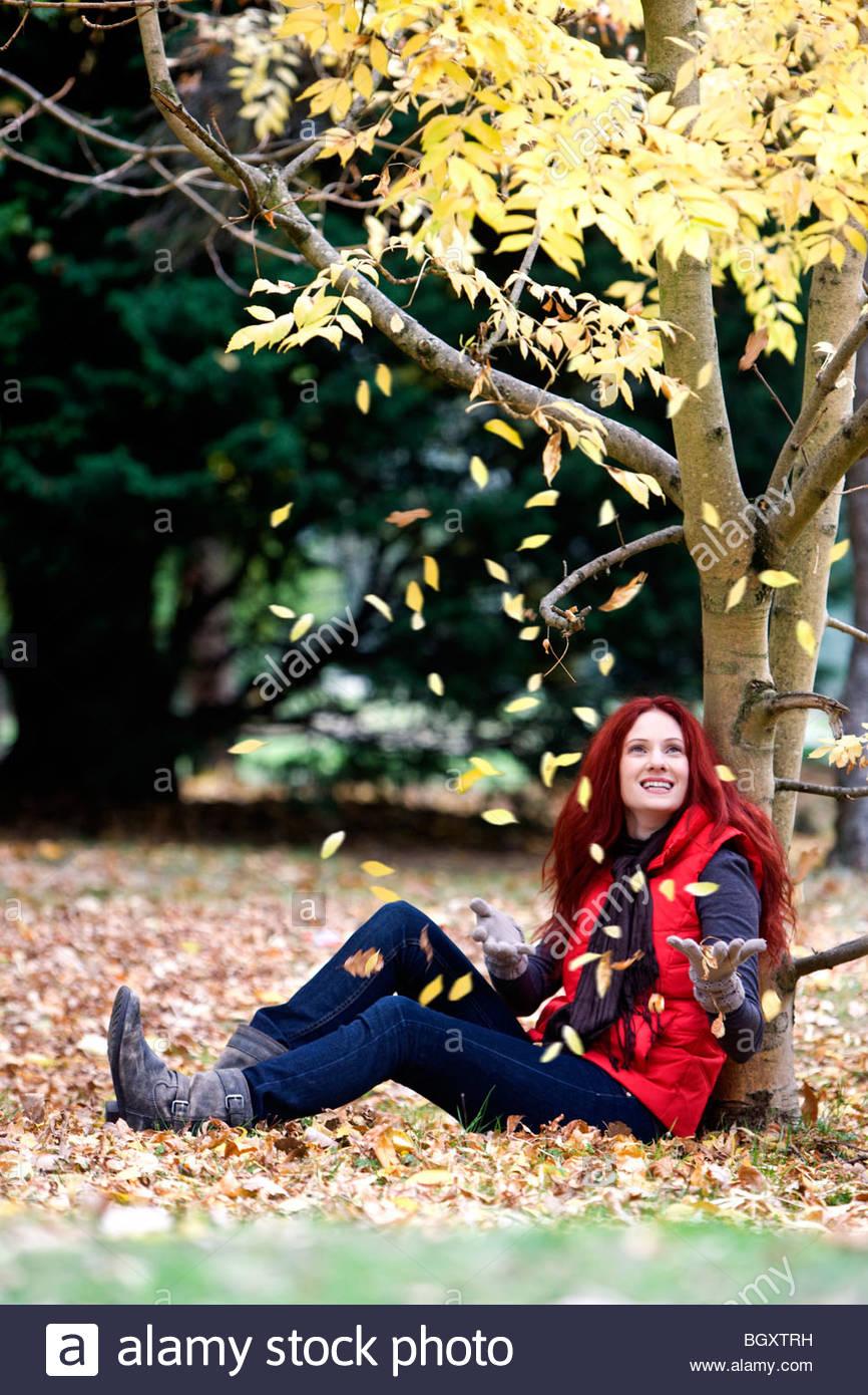Eine junge Frau sitzt unter einem Baum im Herbst Stockbild