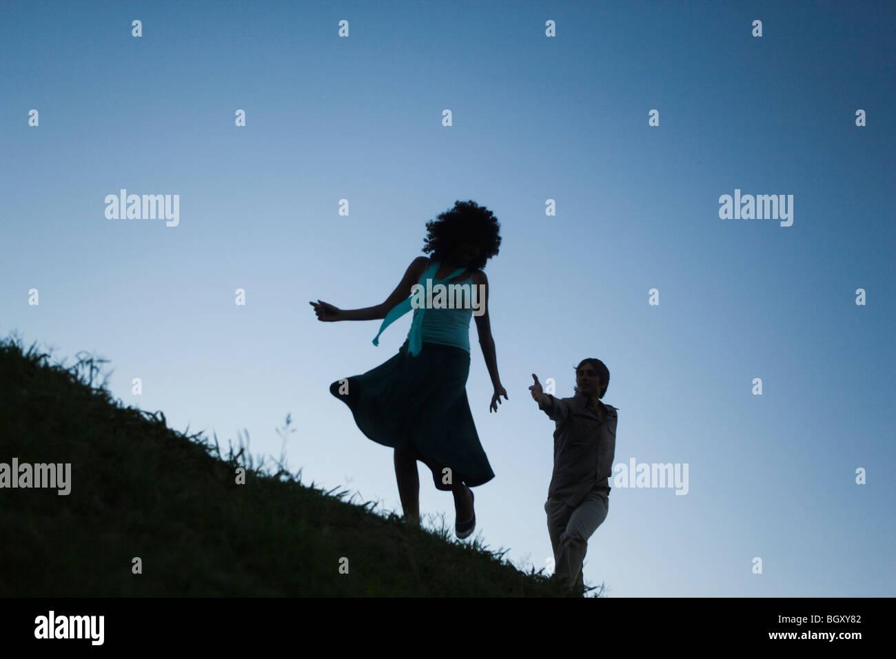 Junge Frau, die spielerisch auf der Flucht vor Mann in der Verfolgung Stockfoto