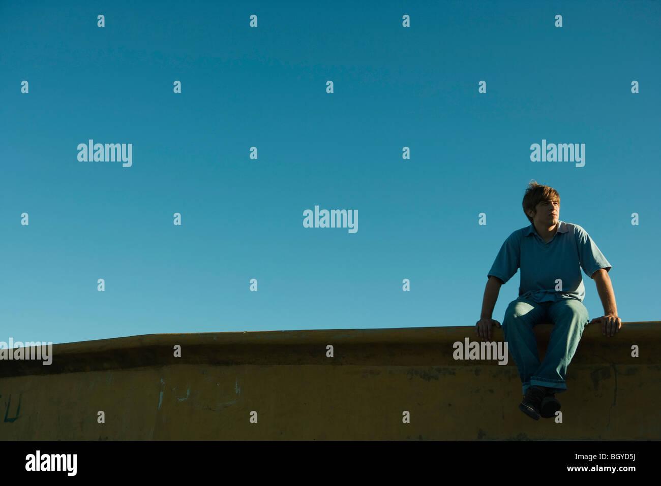 Junger Mann sitzt auf einem Felsvorsprung, wegschauen Stockbild