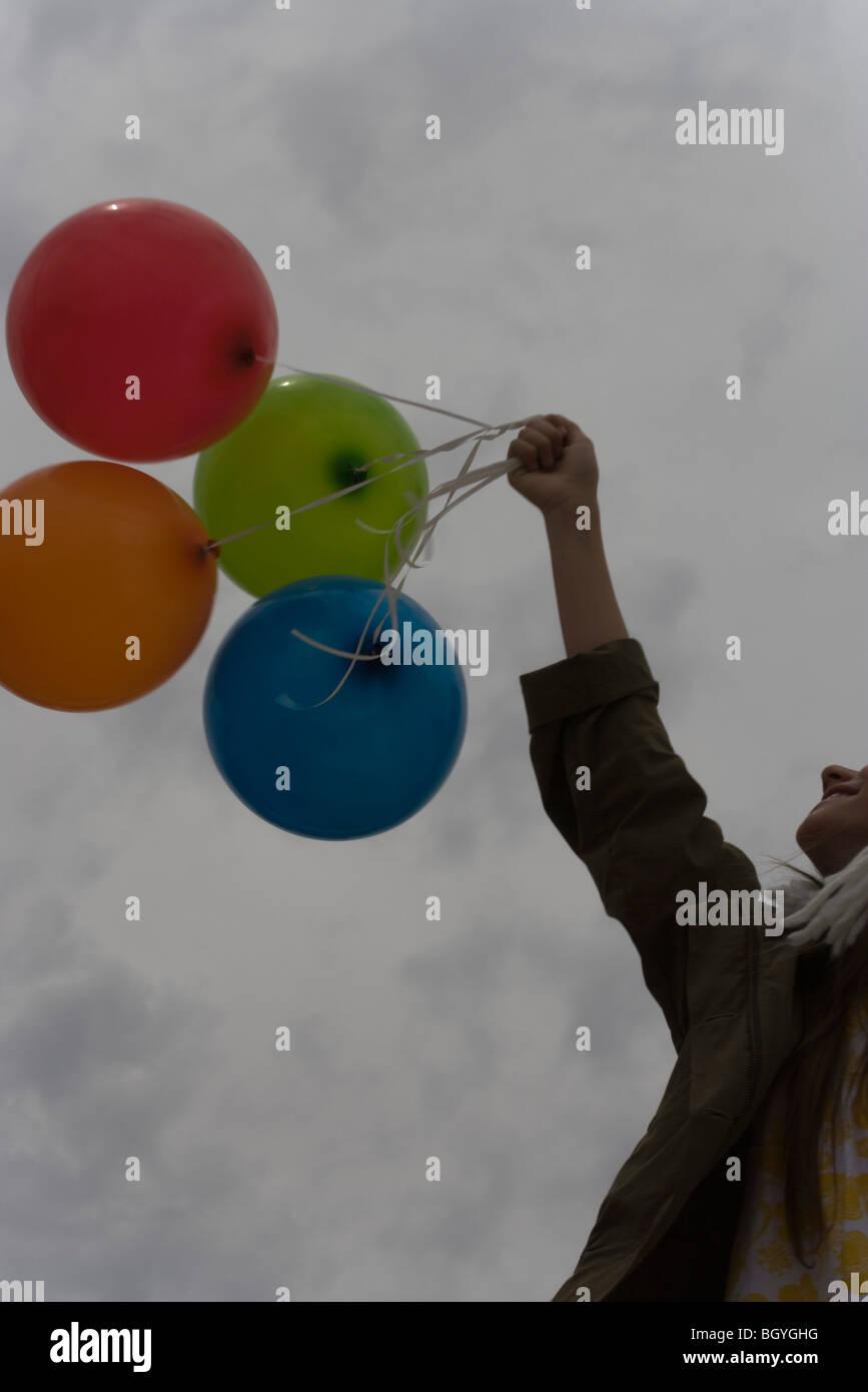 Weiblich, Haufen Luftballons in Richtung bewölktem Himmel hochhalten Stockbild
