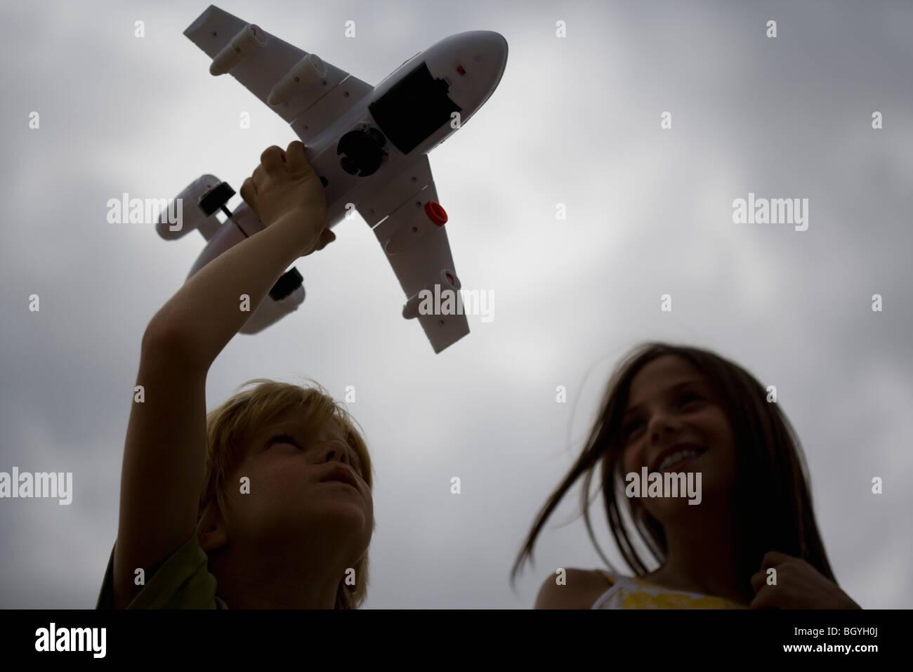 Jungen spielen mit Spielzeugflugzeug, ältere Schwester beobachten, Lächeln Stockbild