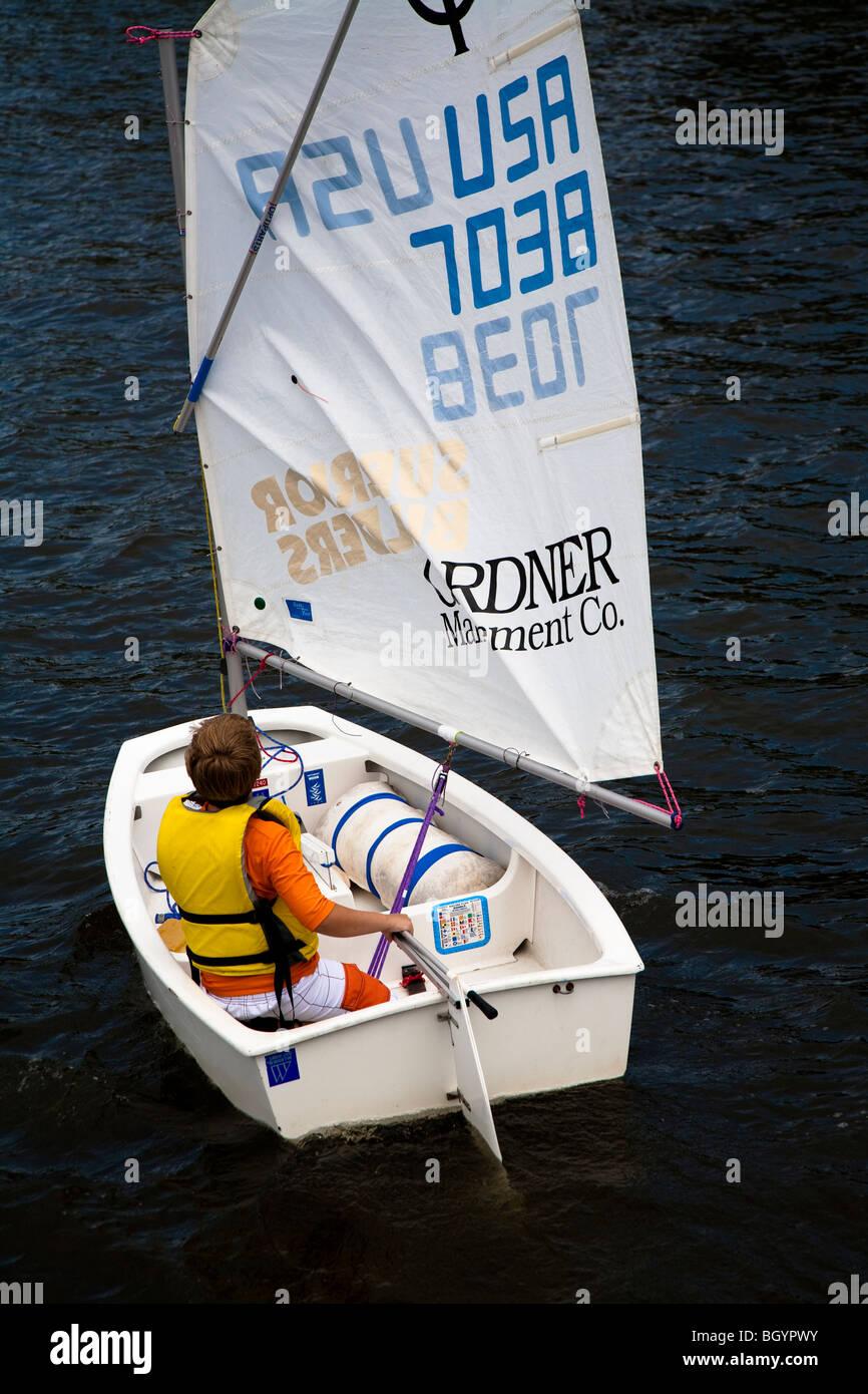 Junge Segler im weißen Optimist Segelboot segeln in St. Joseph, Michigan, USA Stockbild