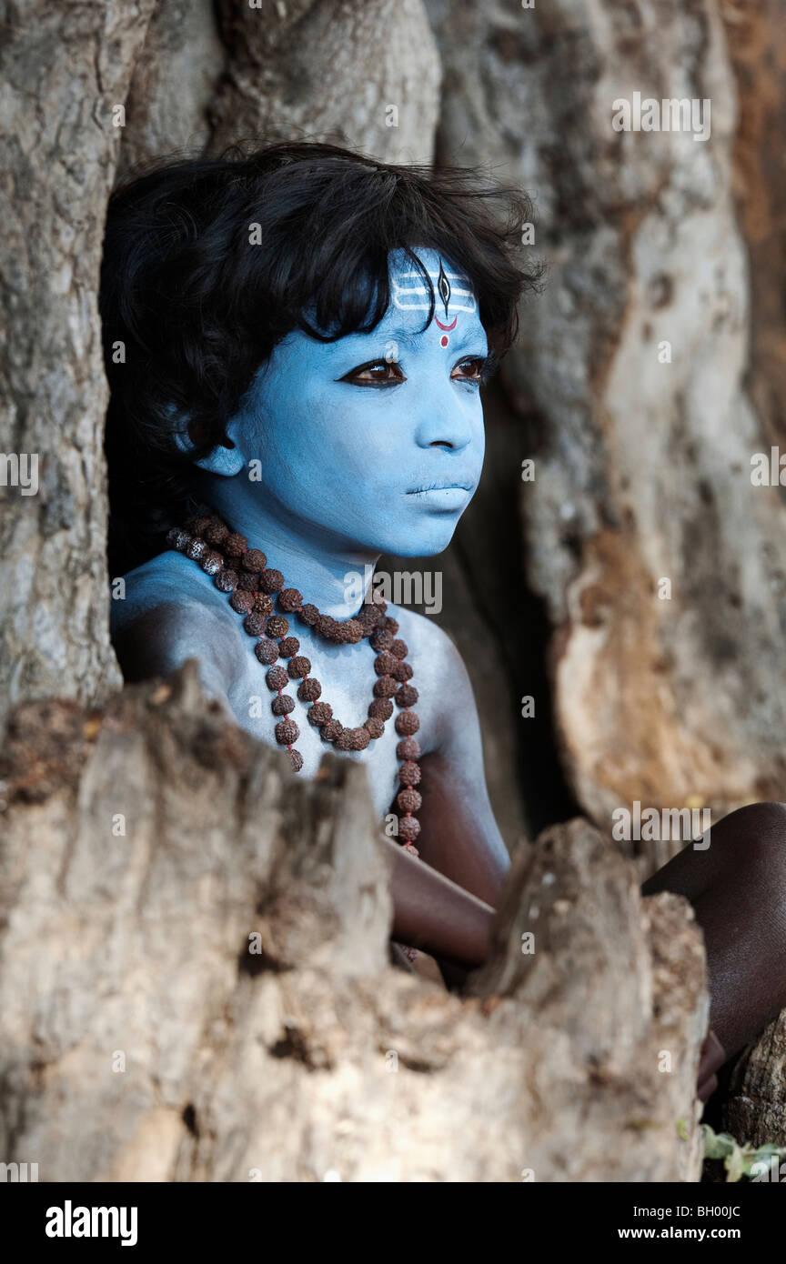 Indischer Junge, Gesicht gemalt als Hindu Gott Shiva in einem alten Baumstumpf sitzen. Andhra Pradesh, Indien Stockbild