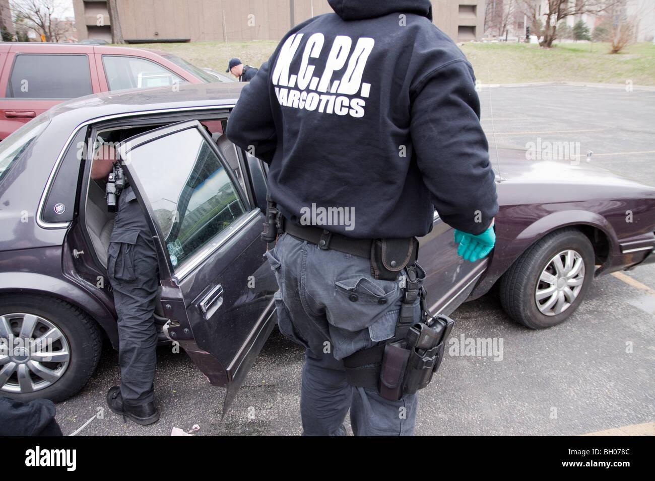 Polizeibeamte suchen Fahrzeug des mutmaßlichen Drogendealer nach der Festnahme des Fahrers. Stockbild