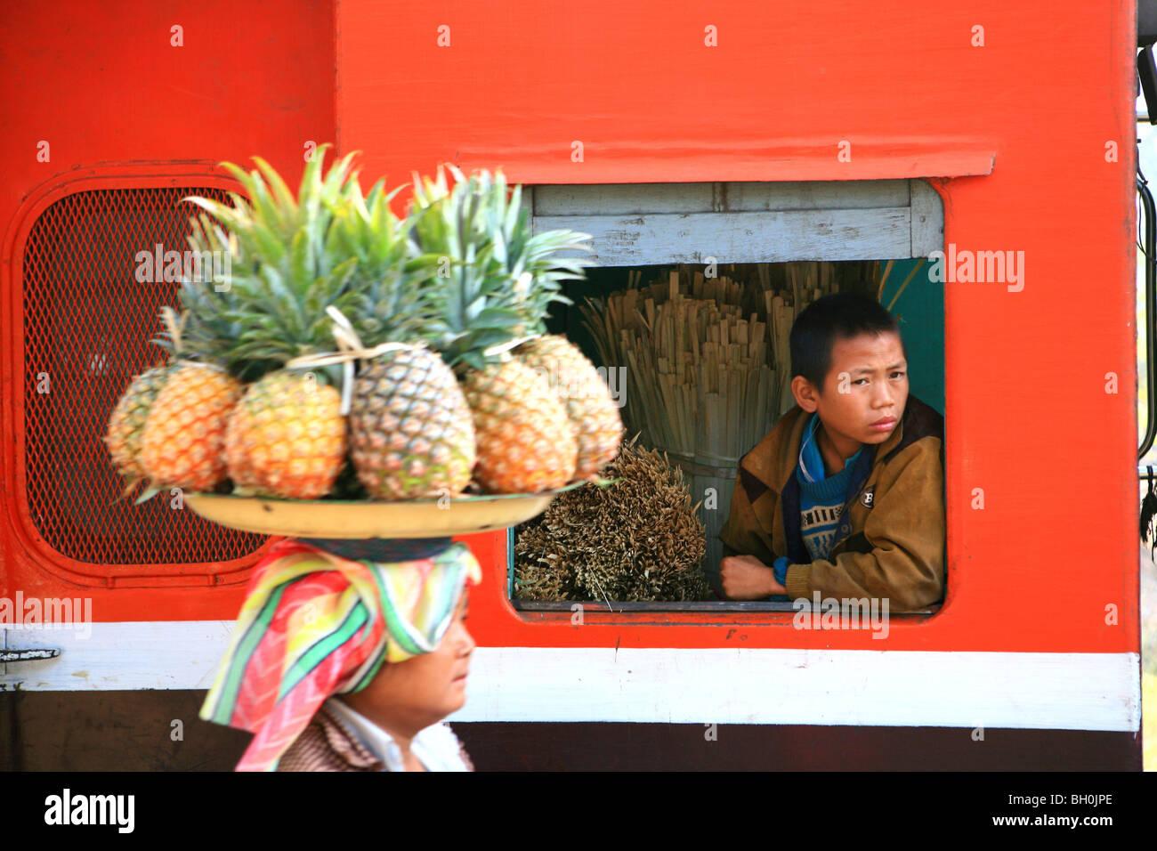 Eine Frau verkauft Frucht, ein Junge aus dem Fenster eines Zuges, Hispaw, Shan State in Myanmar, Myanmar, Asien Stockbild