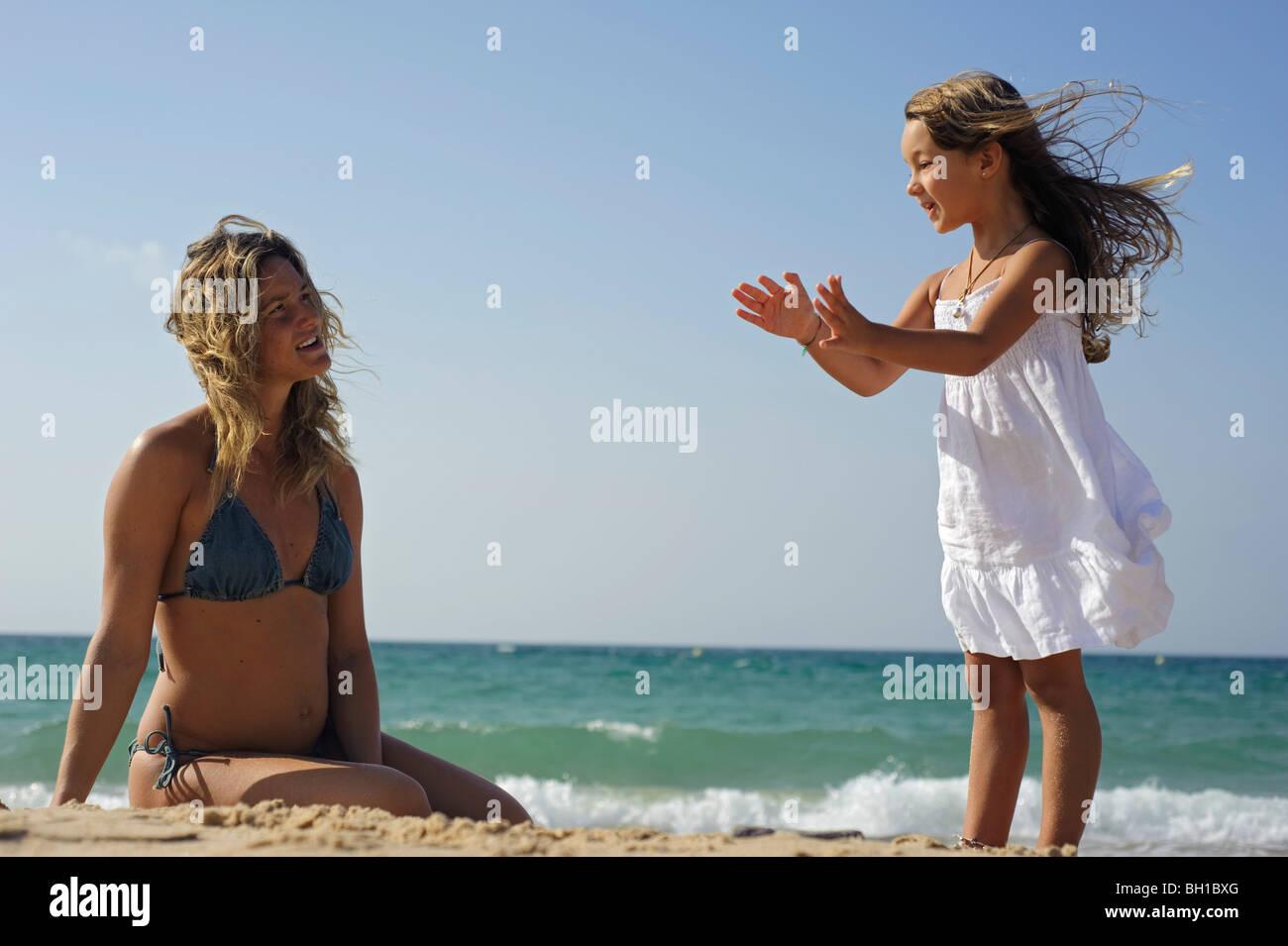 Junges Mädchen mit Mutter am Strand Stockbild